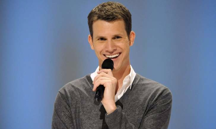 Daniel Tosh giving a big smile while performing onstage