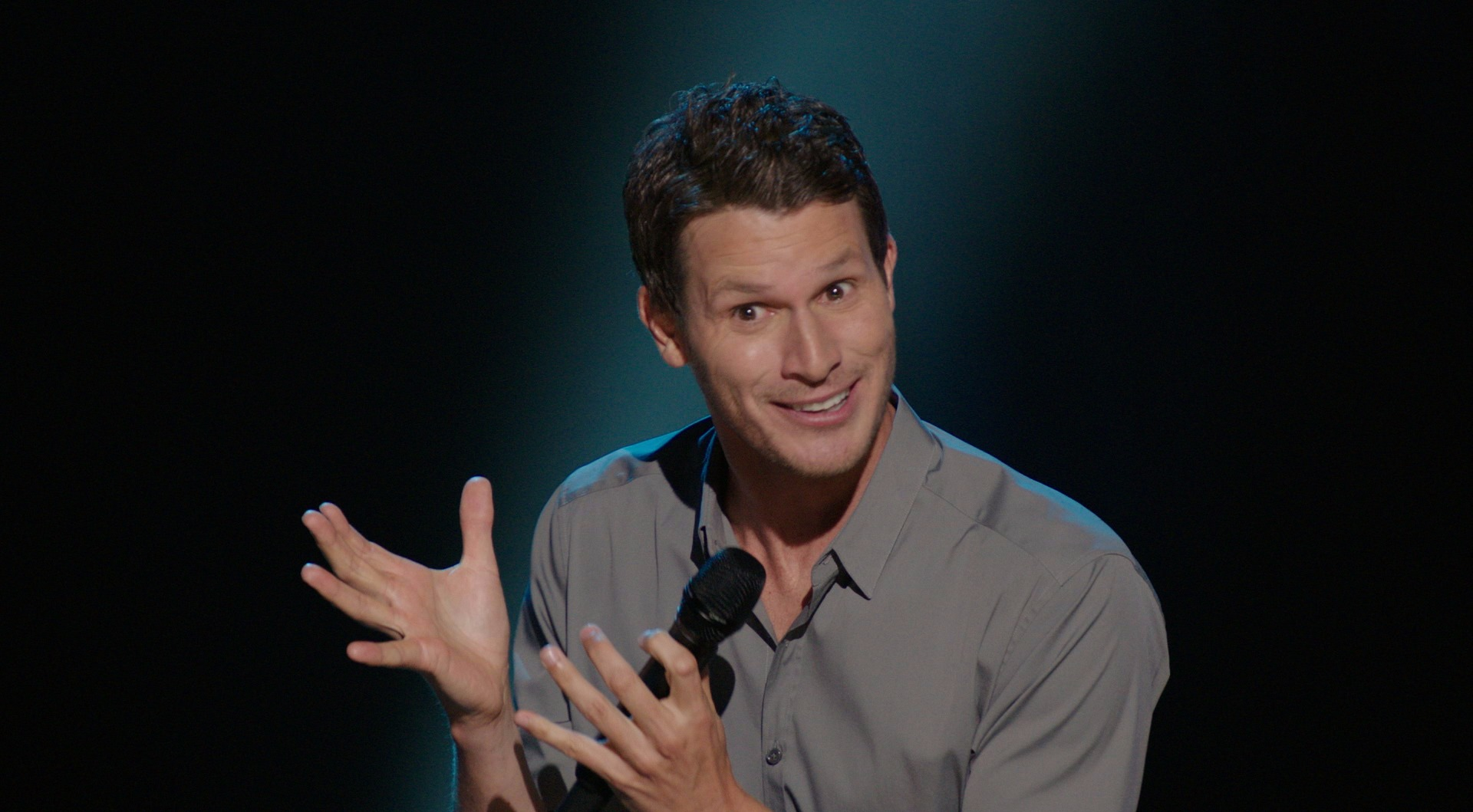 Daniel Tosh giving a funny expression with a mike on his hand as he is performing on his show