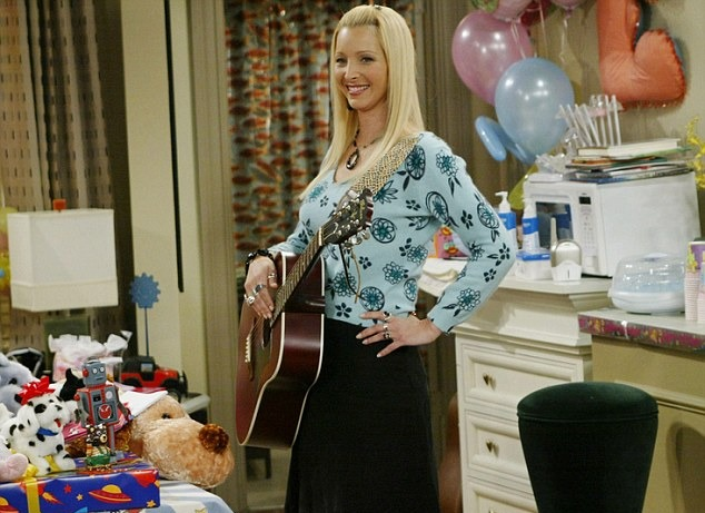 Lisa Kudrow as Phoebe Buffay is holding a guitar in her right hand. She is placing her left hand on the waist with a slight smile on her face.