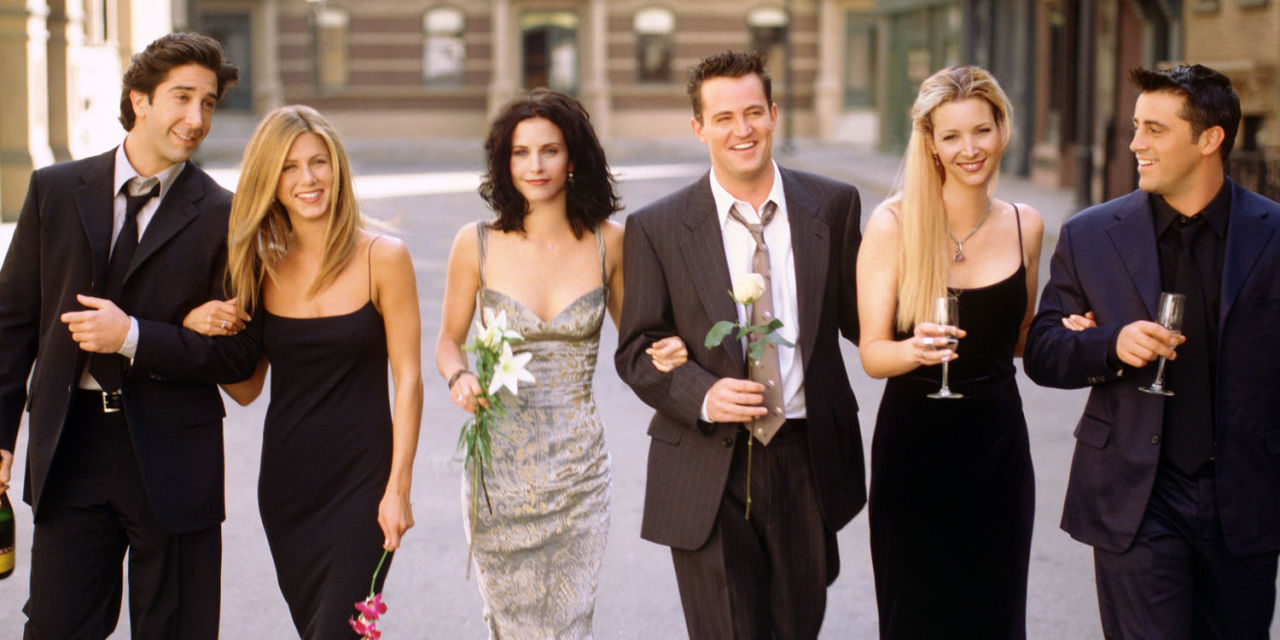 The cast members of NBC's Friends are posing for the camera. David Schwimmer (far left) is holding a hand of Jennifer Aniston. Courteney Cox and Matthew Perry are holding a flower in their hands while Lisa Kudrow and Matt LeBlanc are holding champagne in their hands.