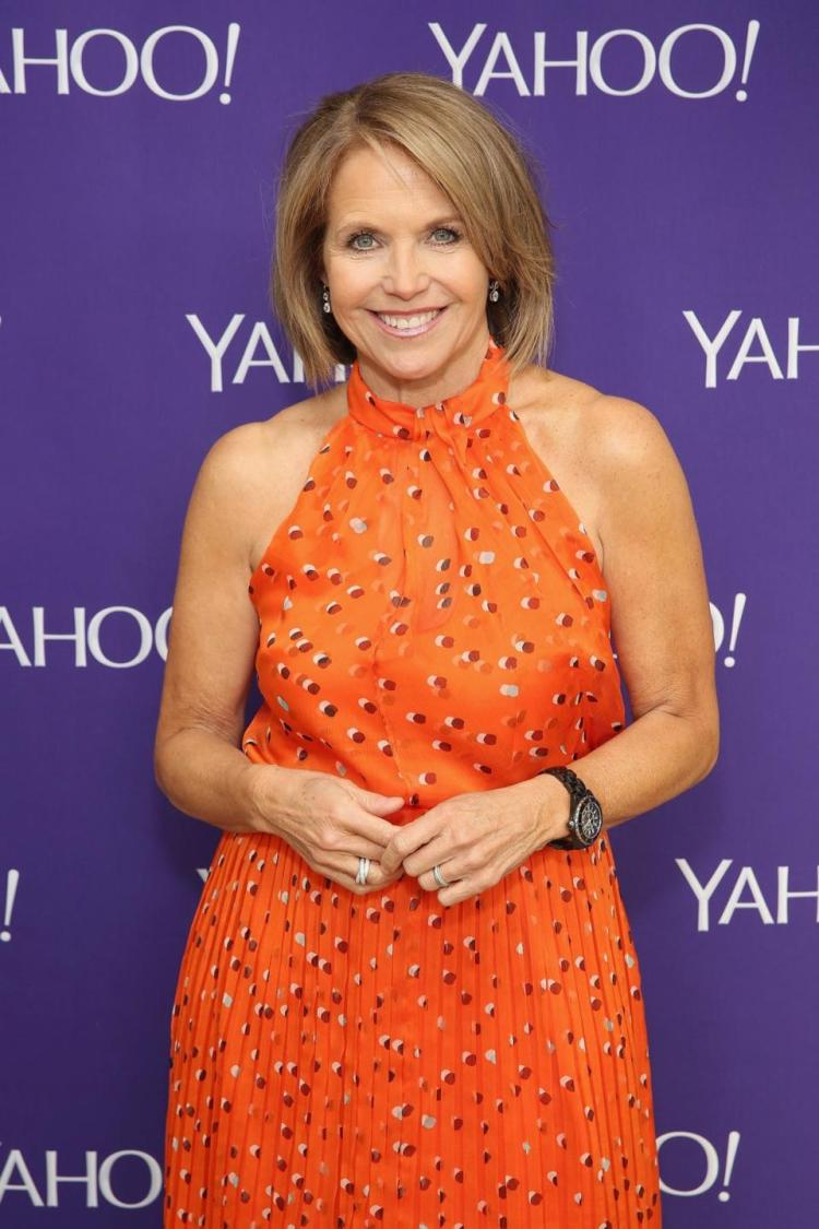 Katie Couric wearing a orange outfit with her hands in the front