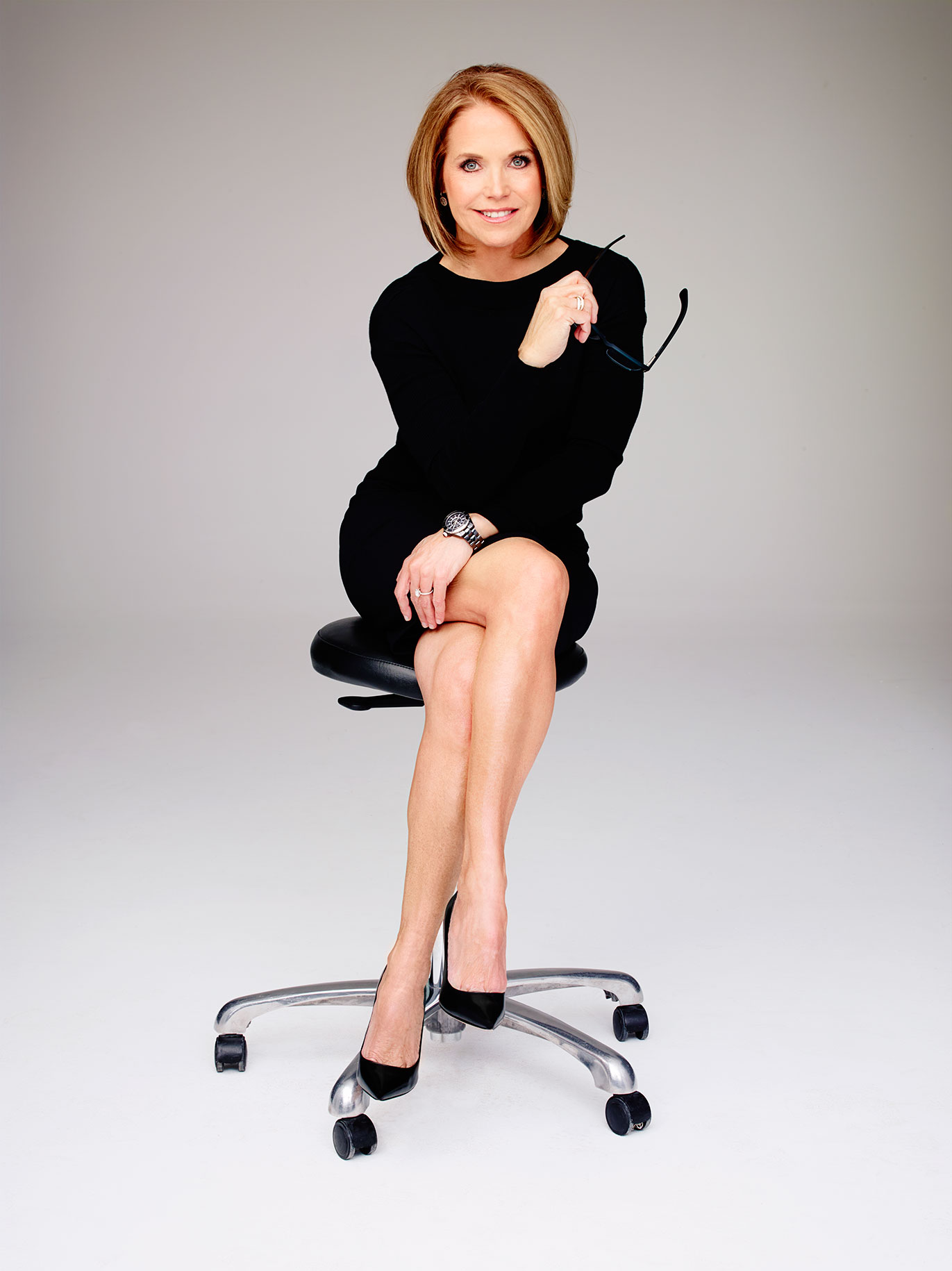 Katie Couric sitting in a chair with her legs folded. She is holding a air of glasses in her hand