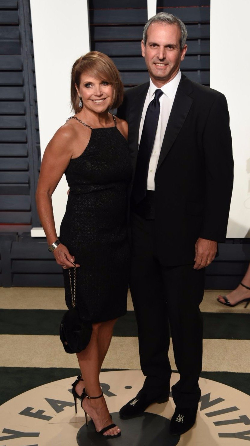 Katie Couric's husband John Molner hugging Katie with one hand while smiling for the picture