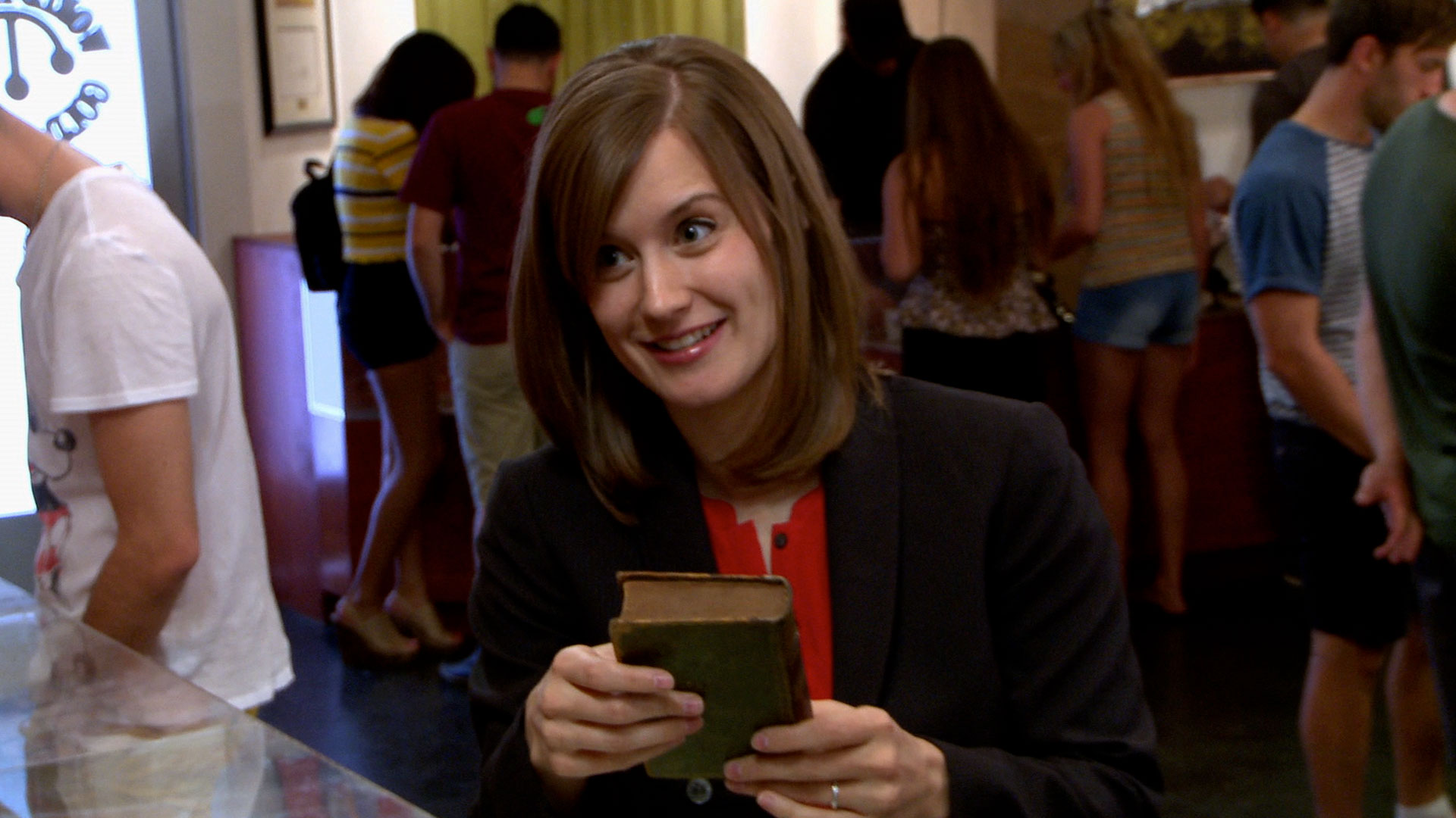 Rebecca Romney at Gold and Silver Pawn Shop holding a book in her hand
