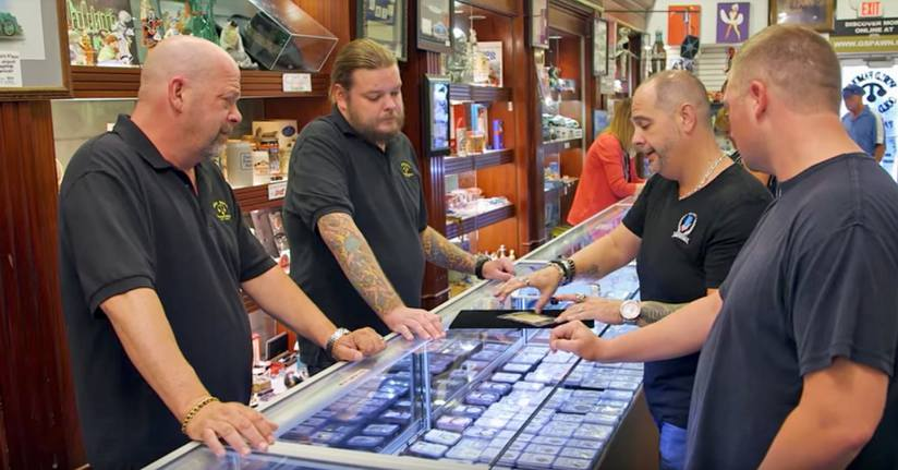Corey Harrison and Rick Harrison looking over an item which two customers are presenting