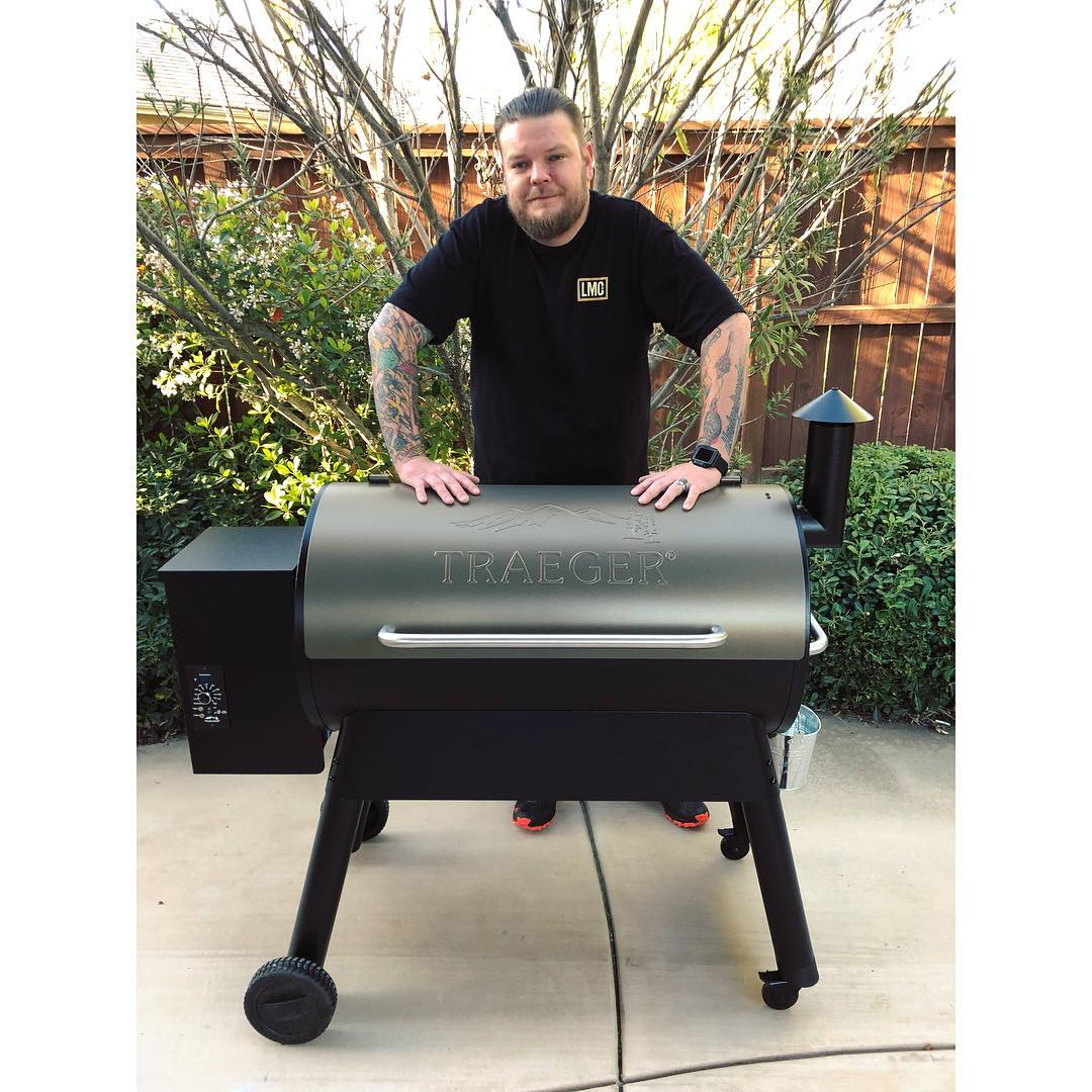 Corey Harrison putting his two hands in a black barbecue machine