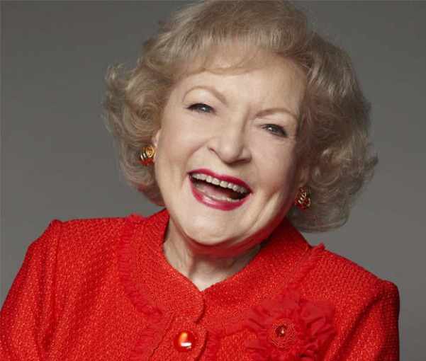 Betty White is on her floral red sweater and she is looking in front of the camera with a big smile on her face. And her golden and red mix earring has added a charm to her face.