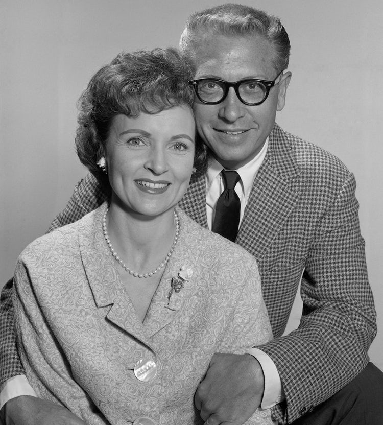 Betty White is with her husband Ludden. They both are posing for the camera looking in front of it with a  delightful smile on both of their face. Ludden is wearing a check suit whereas Betty is wearing a long coat with a flower badge on its color. Similarly, a pearl necklace has defined her face with a extra charm.