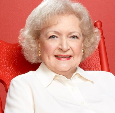 Betty White is carrying a white shirt and she has a platinum blonde hair with a golden earrings on her ear. She is smiling and focusing into camera with a pose sitting in a red colour chair.
