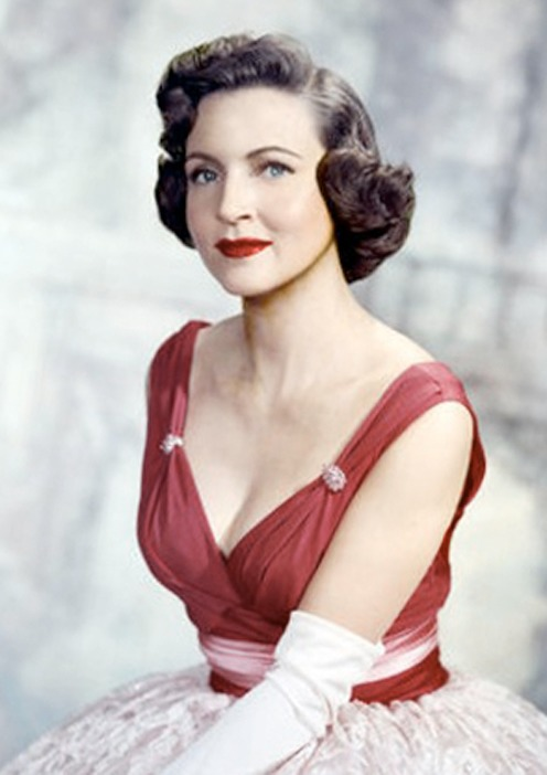 Betty White is wearing a red and white backless glamorous gown. She is wearing a gloves on her hands. She has a black short curved hair. She is focusing into camera with a  graceful style.