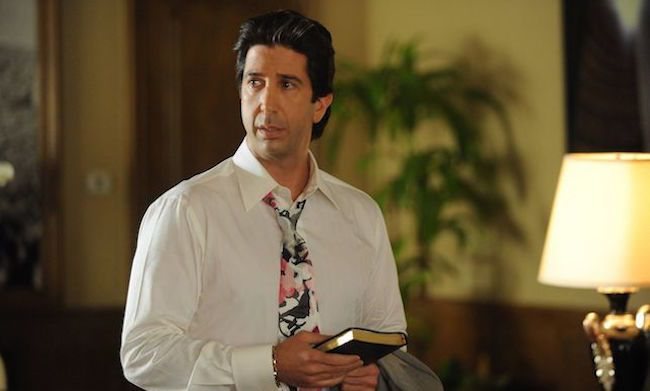 David Schwimmer in the set of American Crime Story. He is holding a book in his hand. He is wearing a white shirt and a tie.