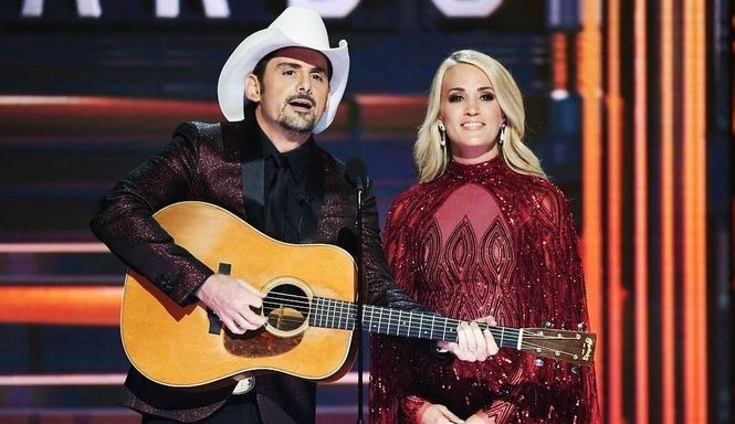 Carrie Underwood standing on the stage in front of stand-mic with her CMA co-host Brad Paisley. She is wearing a blue-net dress and Brad is holding a guitar in his hand.