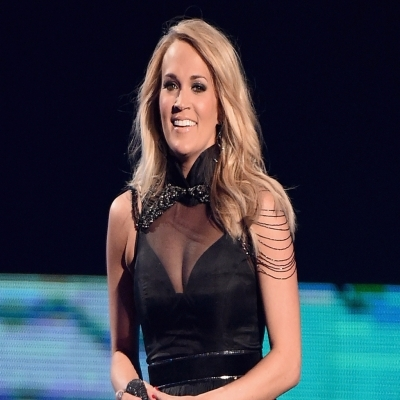 Carrie Underwood looks hot in the black dress. She is smiling looking at the camera.