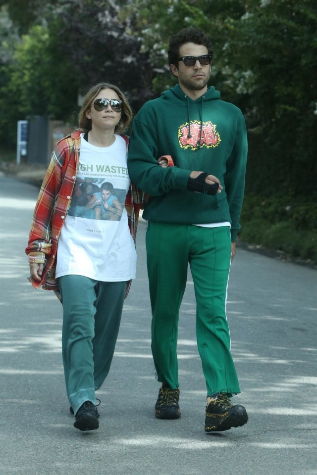 Ashley Olsen wearing a pair of sweatpants and a red flannel over an oversized printed T-shirt and Louis Eisner is wearing an entire green attire. They are walking arm-in-arm.
