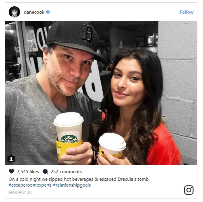 Dane Cook taking a selfie with his much younger girlfriend Kelsi Taylor. The two are holding beverages on take away cups.