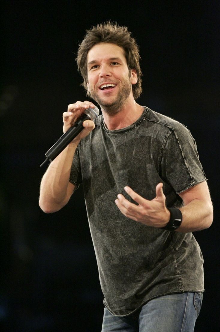 Dane Cook is holding a mic in his right hand. He is looking away from the camera delivering his performance.