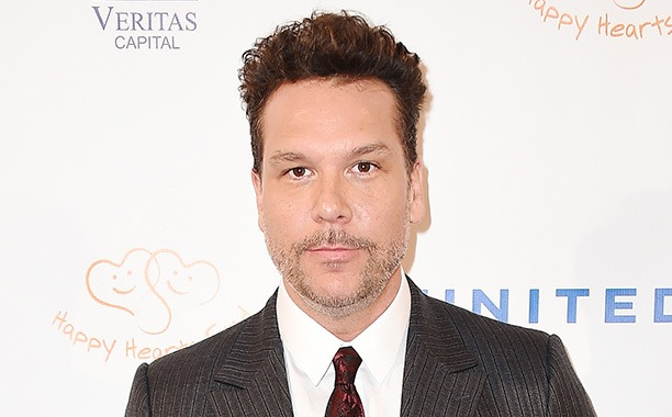 Dane Cook is facing the camera with a serious look on his face. He is wearing a white shirt, printed tie and grey suit.