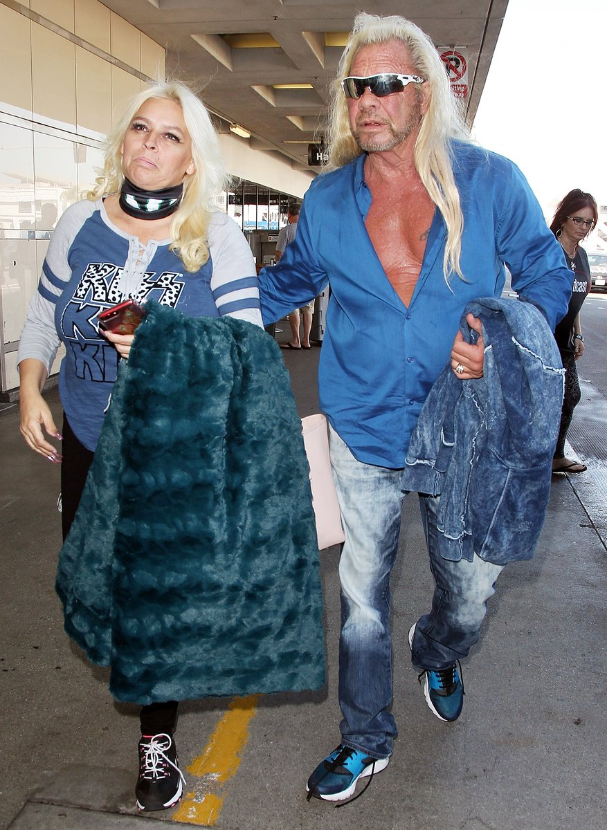 """Duane Lee """"Dog"""" Chapman walking with his wife holding jacket in their hands"""