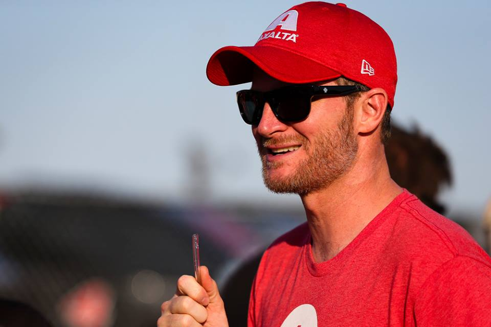 Dale Earnhardt Jr. is wearing red t-shirt, rap, sun glass and is holding a pipe in his hand