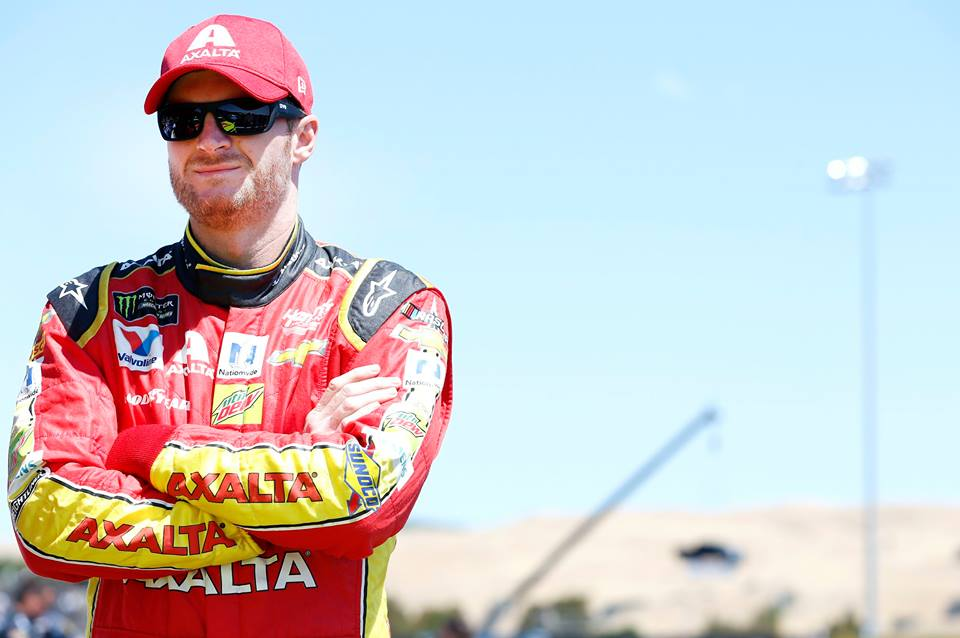 Dale Earnhardt Jr. standing with his hands folded in his racing suit