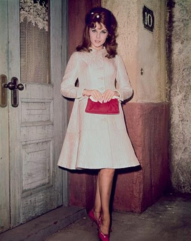 Ann Margret is posing gracefully, crossing her legs and holding a purse. She is standing outside a home.