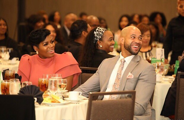 Fantasia Barrino accompanied by her husband in a event, they are sitting in a table and are both laughing. Fantasia is wearing a peach coloured dress and her husband is well suited in grey and white combo.
