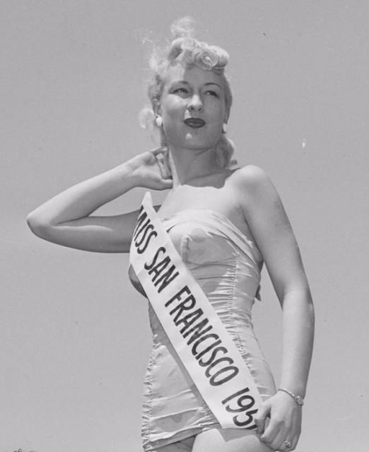 Barbara Eden posing keeping her hands behind her neck with the sash of Miss San Francisco 1951