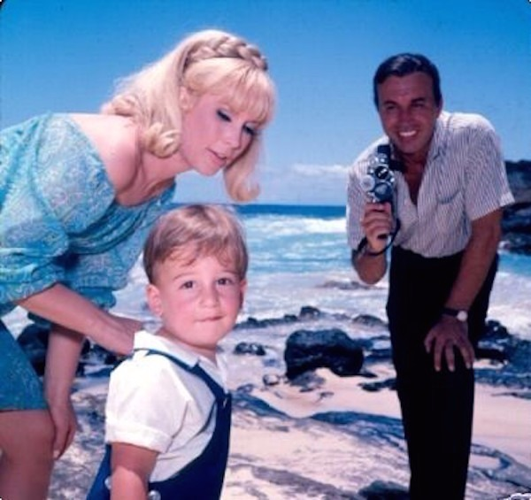 Barbara Eden holding her son who is facing the camera while husband posing with a smile