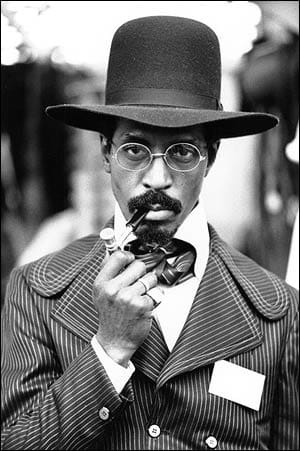 Ike Turner during his young age. He is smoking a pipe. He is looking classic in his black hat and antique coat and tie.