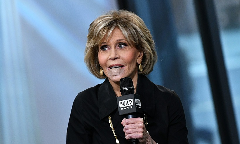 Jane Fonda is appearing in a show wearing a black shirt and a golden chain. She is holding a microphone in her left hand trying to speak. Her bottom lip is covered with a bandage.