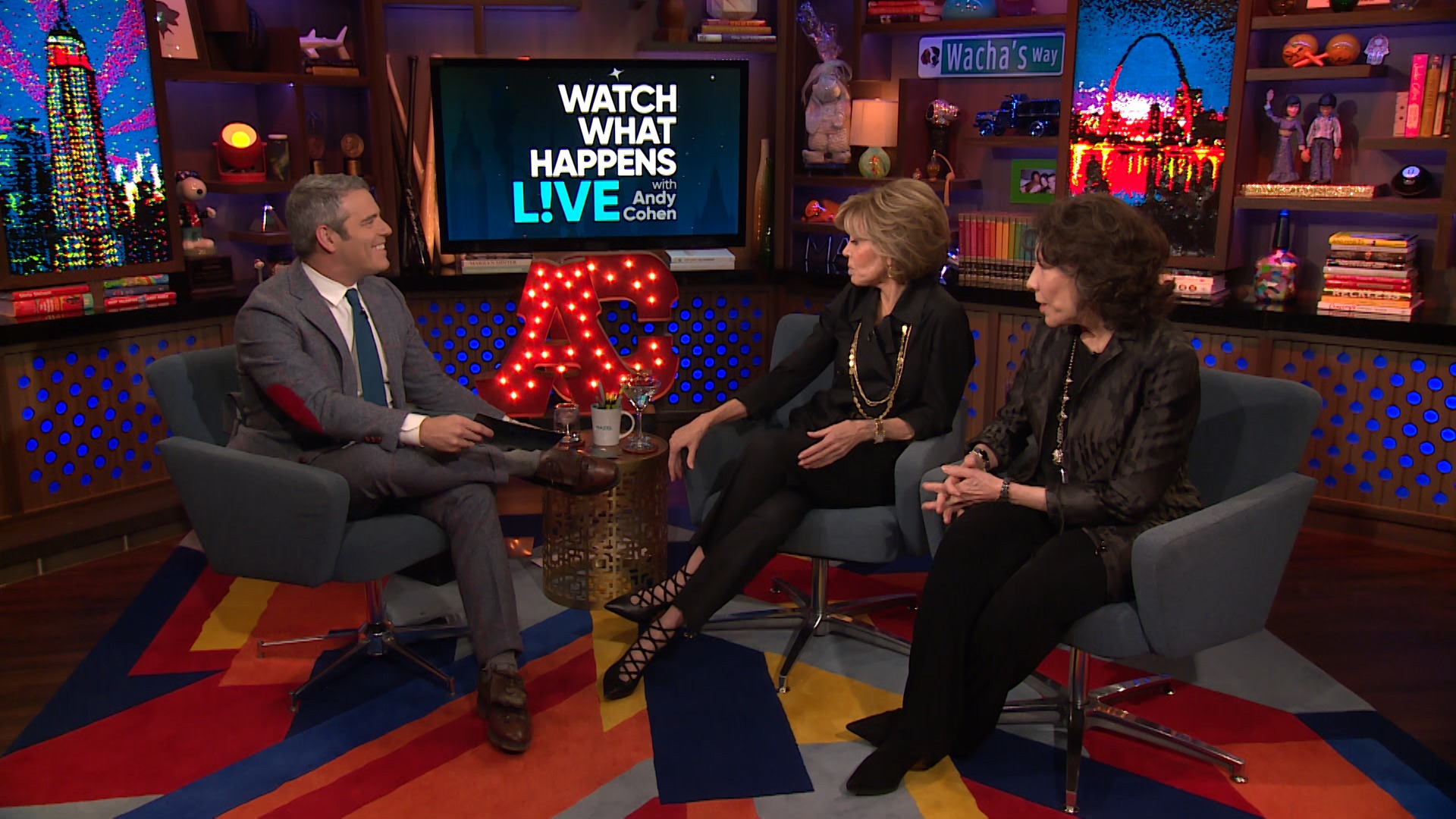 Jane Fonda is on the set of What Happens Live. On her company is the host Andy Cohen on the left side and Lily Tomlin on the right. She is in a full black attire. They're having a conversation. Therefore, Jane and Lily are facing the host.