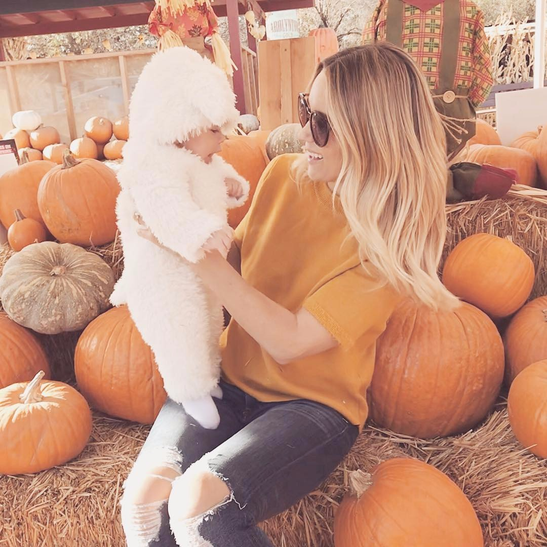 Lauren Conrad holding her new born son. She has dressed her son in a ship like onesie. They are visiting the pumpkin patch.