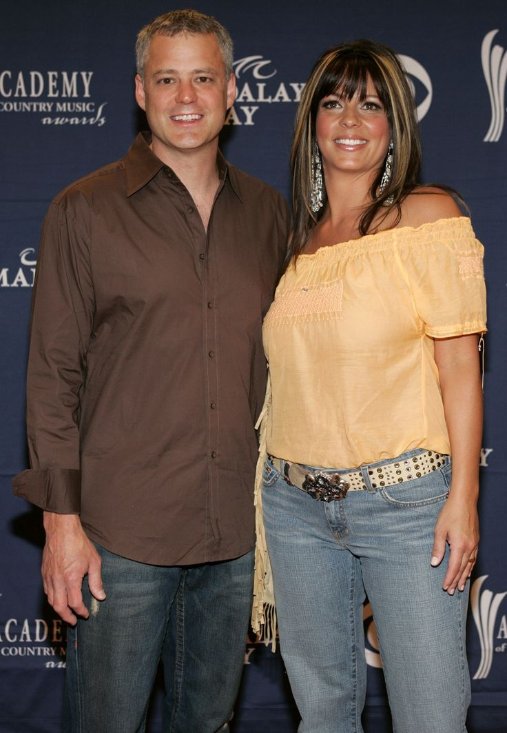 Sara Evans is standing close to Craig Schelske for a picture. She is seen sporting a yellow top