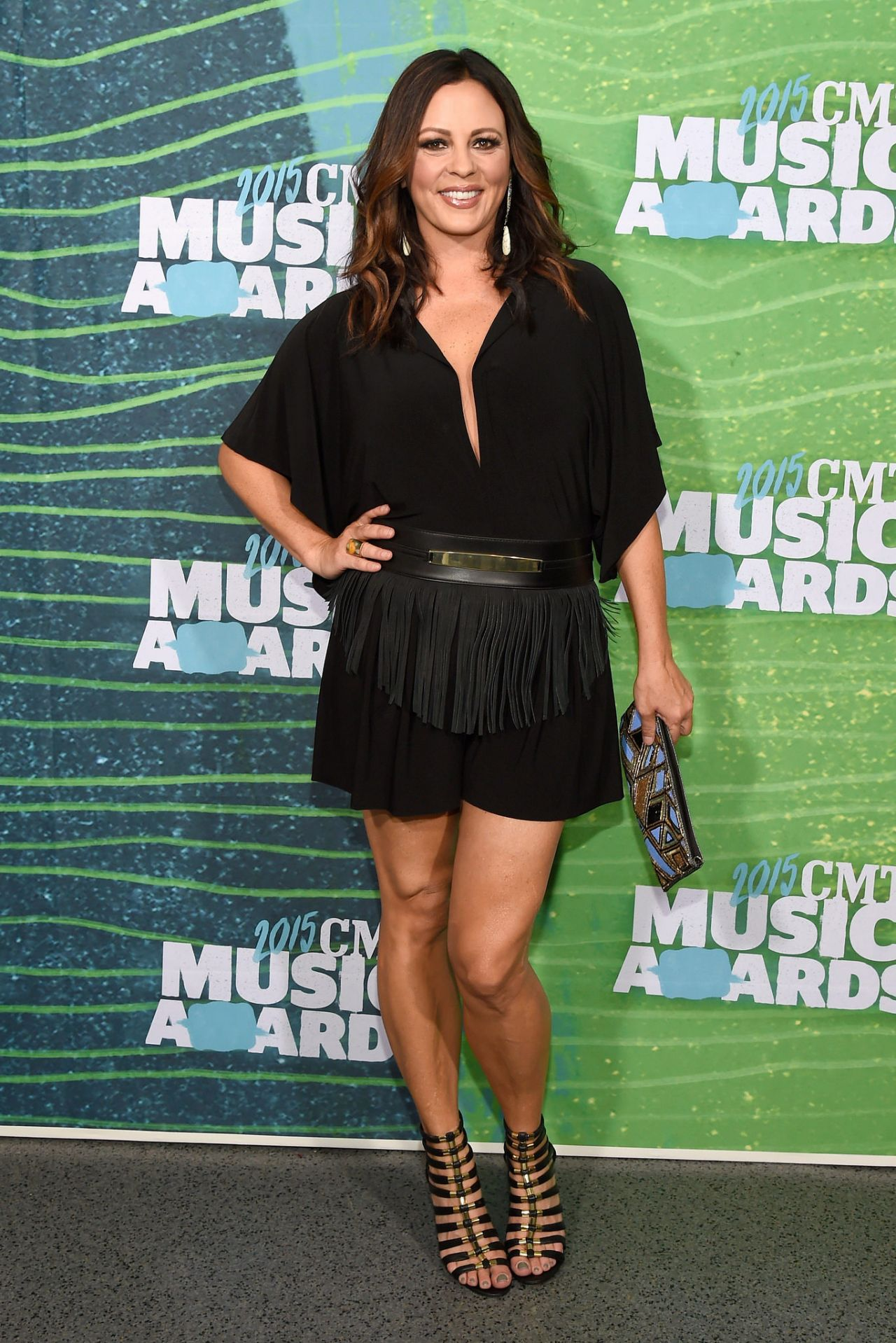 Sara Evans wearing a black dress and holding a purse in her hand.