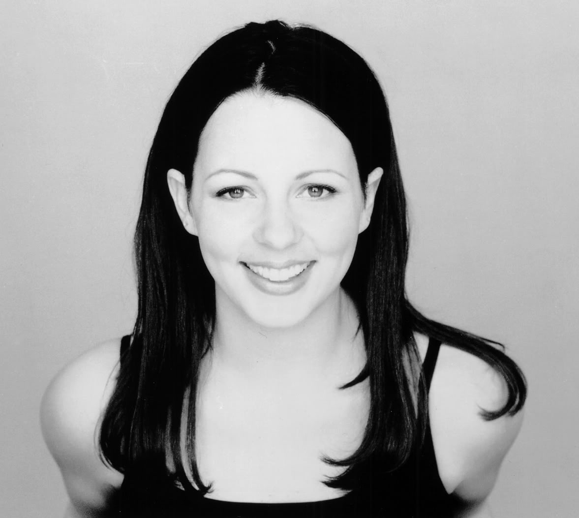 Sara Evans in a black tank top and long hair. She is smiling in the picture.