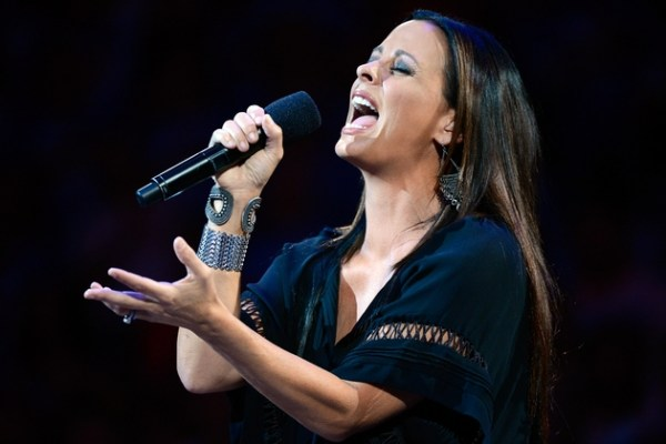 Sara Evans singing at a live event. She is holding a mike with a hand and swinging another