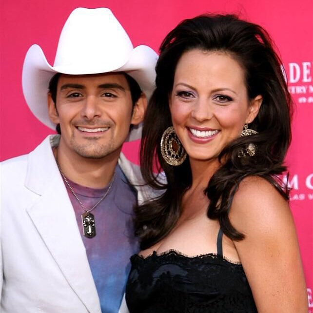 Sara Evans stands close to Brad paisley while they pose for a picture. Sara Evans is wearing a black top while Brad is wearing a white hat and white coat
