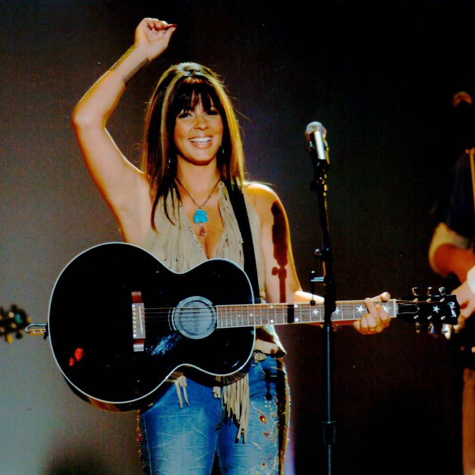 Sara Evans playing the guitar at one of her concerts