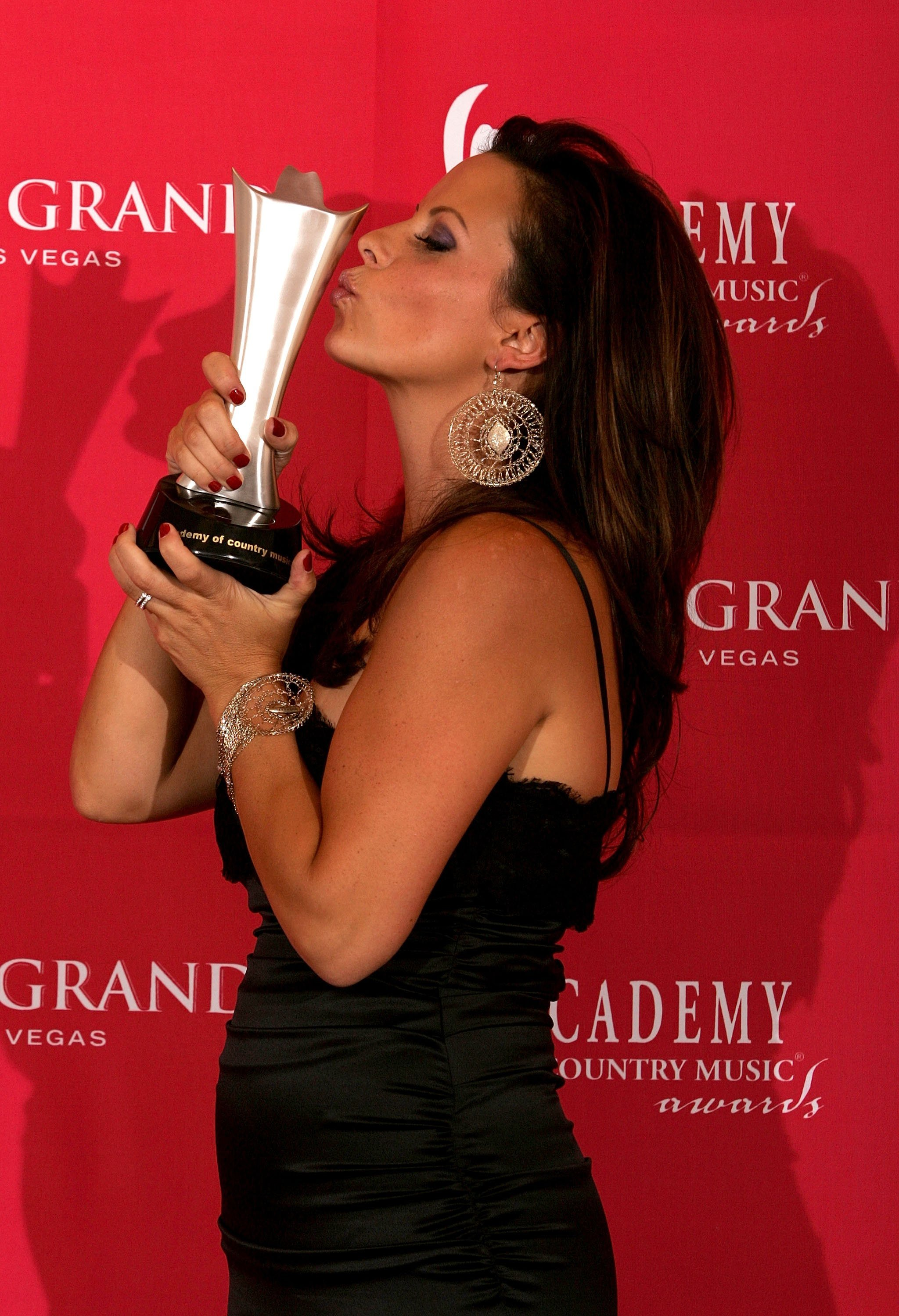Sara Evans holding her award with both hands and kissing it