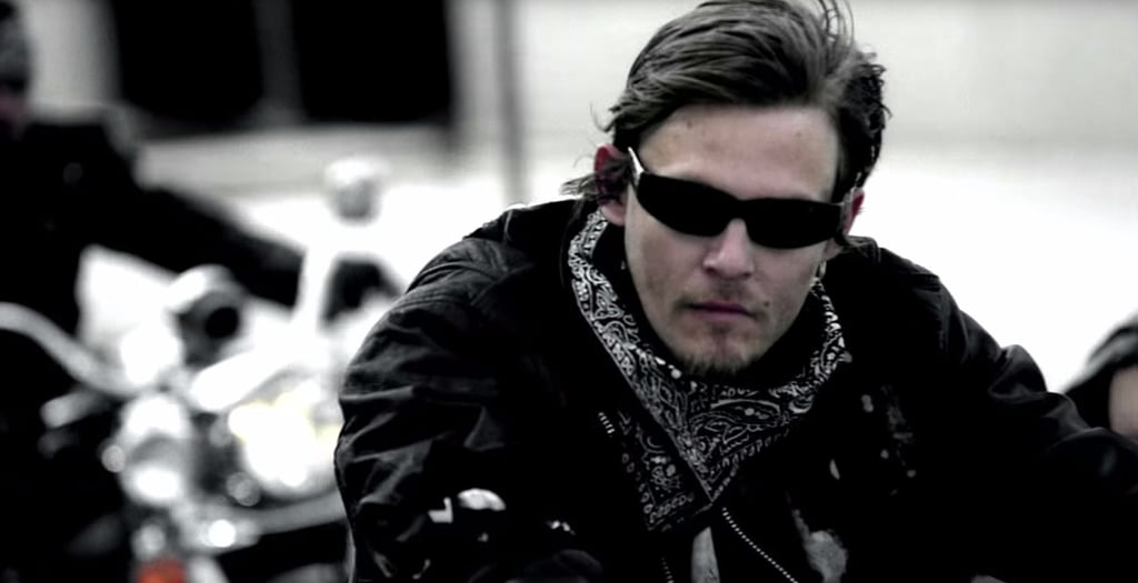 Norman Reedus wearing black spectacles and a scarf around his neck. He is sitting on the bike.