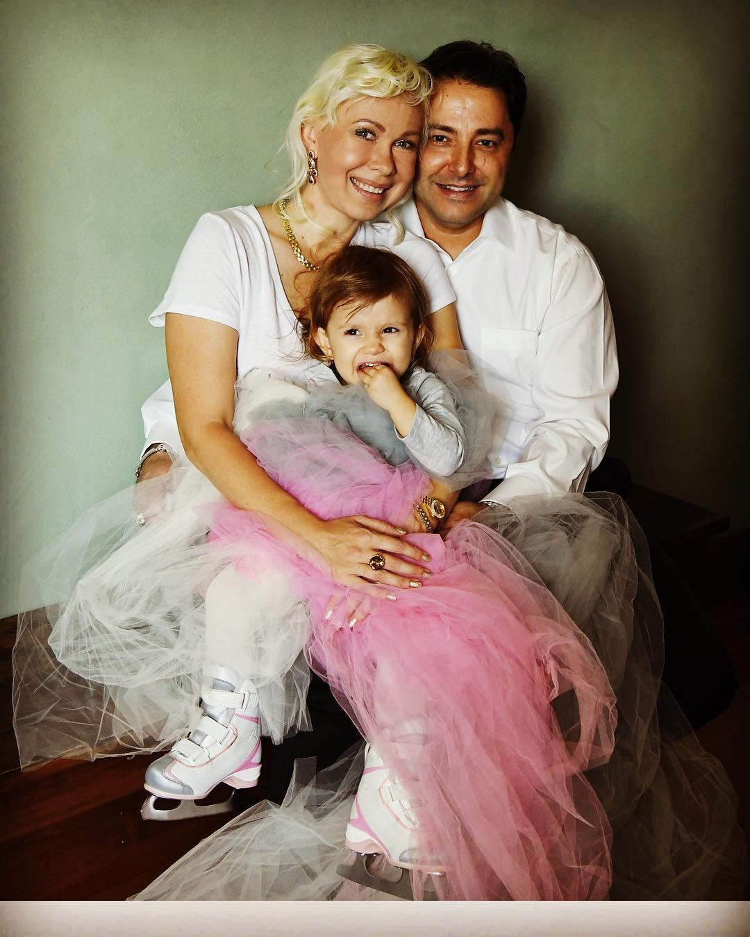 Oksana Baiul sits alongside her husband and her daughter.