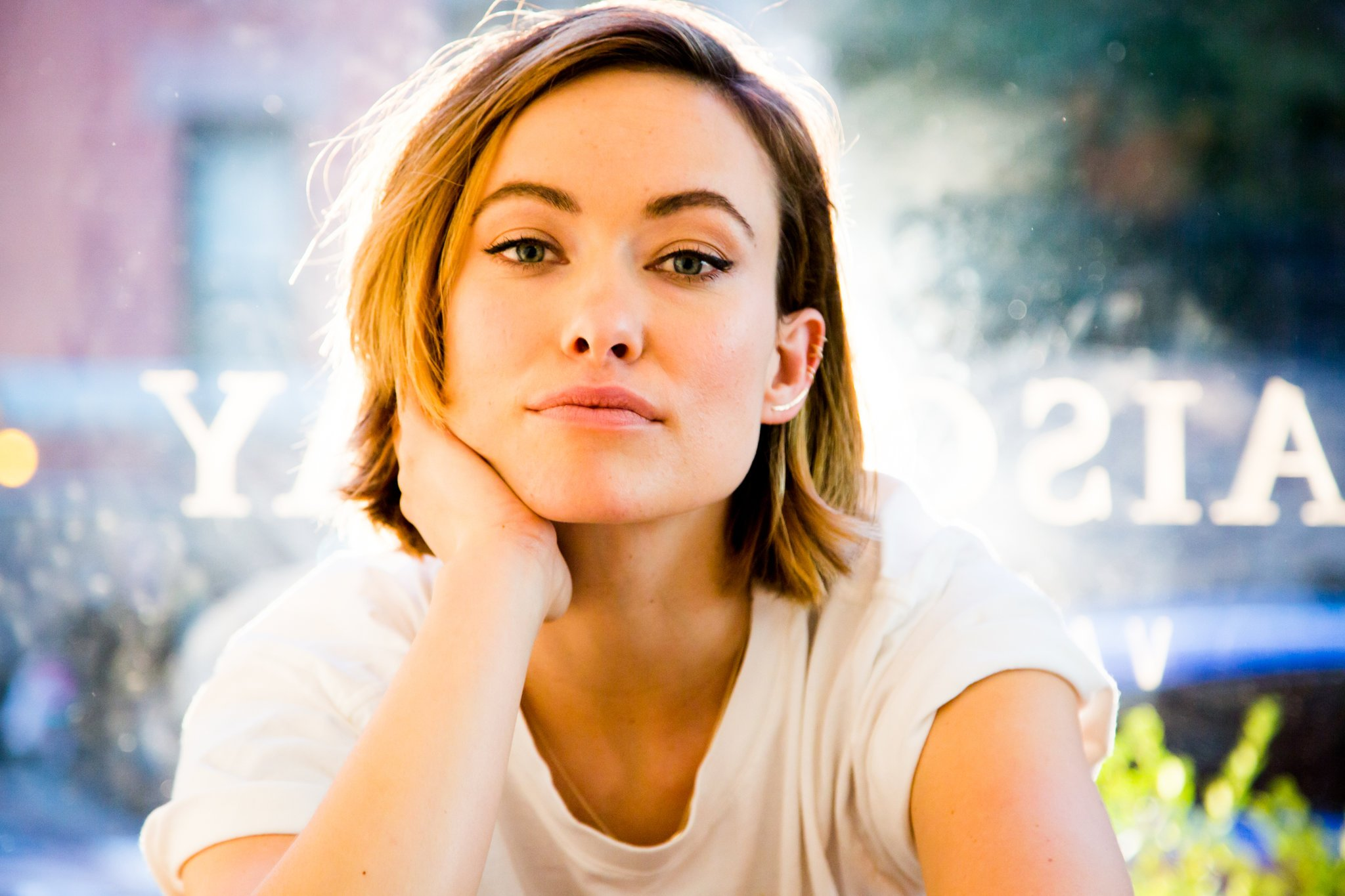 Olivia Wilde has short blonde hair and is wearing a white t-shirt