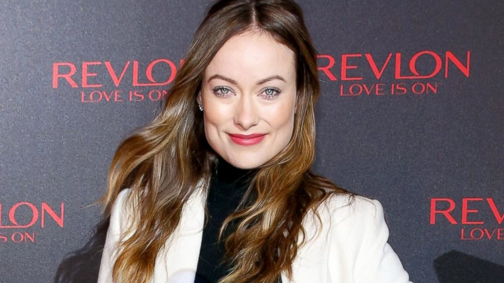 Olivia Wilde is wearing a white coat and black hi-neck