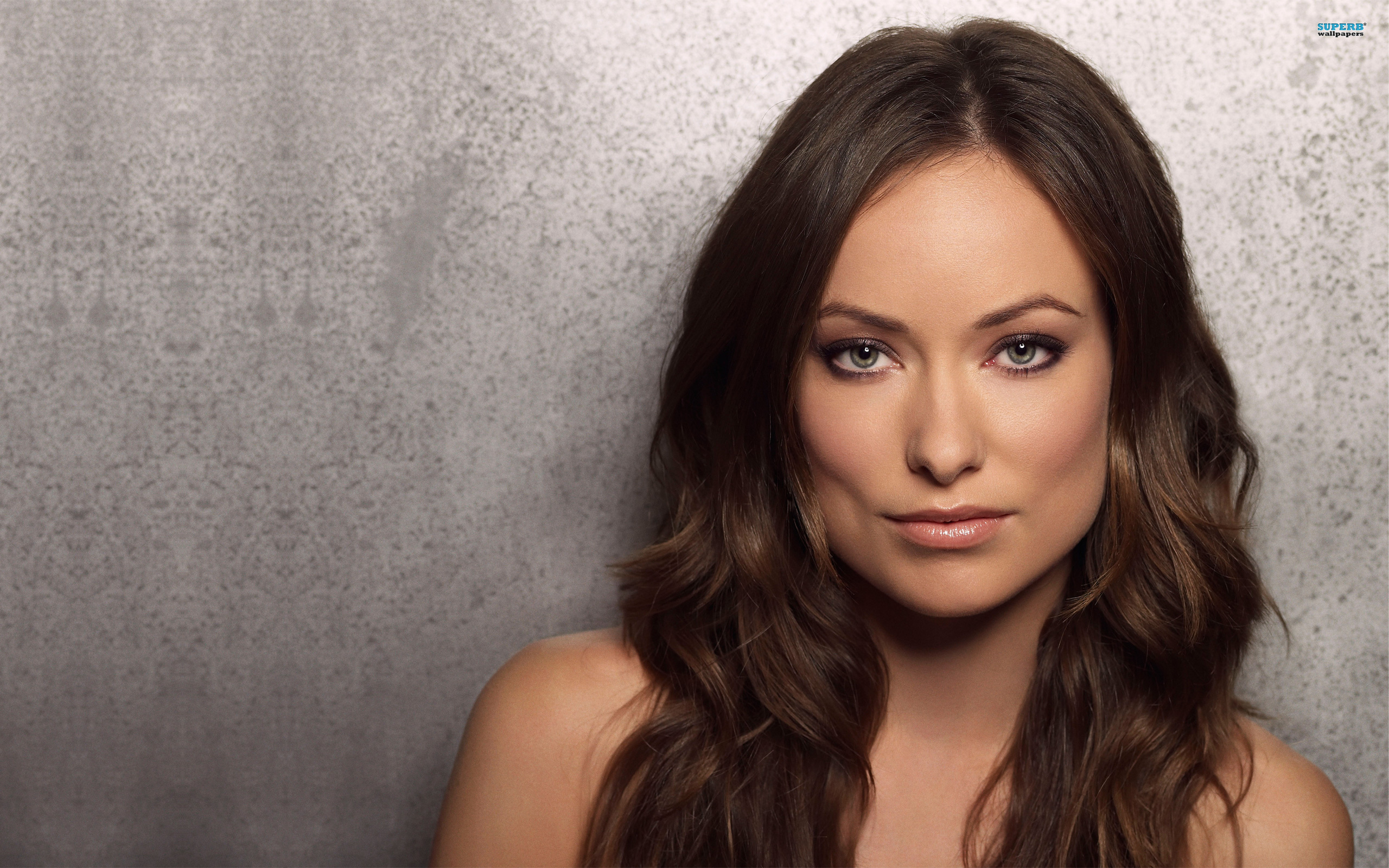 Olivia Wilde has long hair and is leaning on the wall