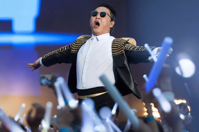 Psy on stage with arms wide open, he's wearing a military jacket and glasses