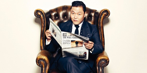 Psy sitting on a chair, holding  a newspaper