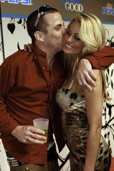 Steve-O is kissing his ex-wife Brittany McGraw in her chicks while holding a beer cup in one hand and hugging her with the other