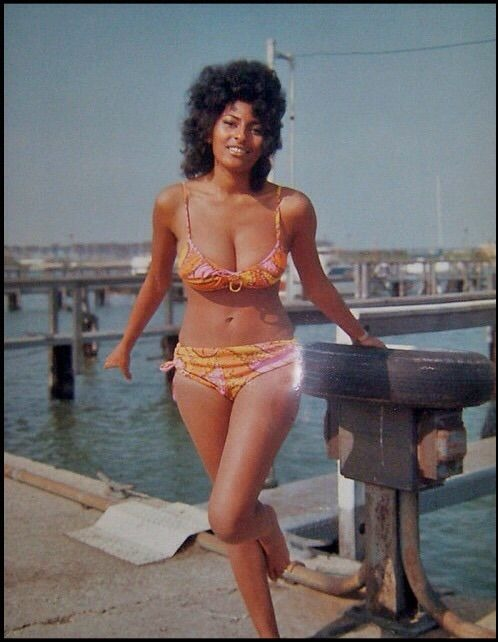 Pam Grier in the iconic yellow colored bikini. She is looking at the camera with a poise on her face. Her legs look so luscious.