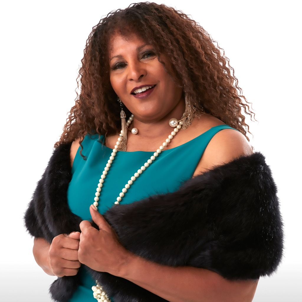 Pam Grier still looks beautiful and attractive in her 60s. She wearing a blue dress and furry outer which is complemented by the pearl neck piece and curly hair.