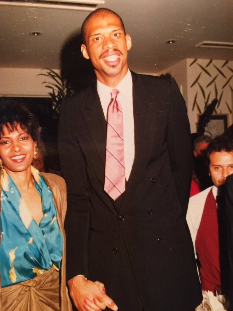 Pam Grier and Kareem Abdul-Jabbar are holding hands.